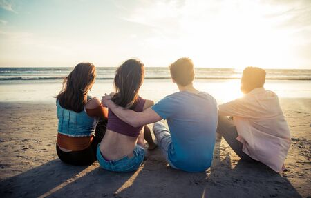 sitting people: Four friends enjoying the sunset at the beach