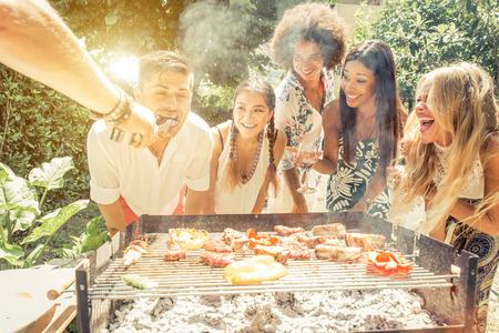 hombre comiendo: Grupo de amigos de la raza mixta hacer barbacoa en el patio trasero y celebrar con un buen estado de ánimo Foto de archivo