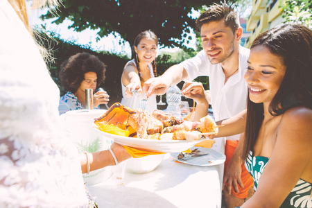 airiness: Group of mixed race friends making barbecue in the backyard and celebrate with good mood Stock Photo