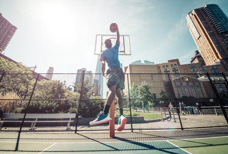 Street basketball athlete performing huge slam dunk on the court, New york buildings background Standard-Bild