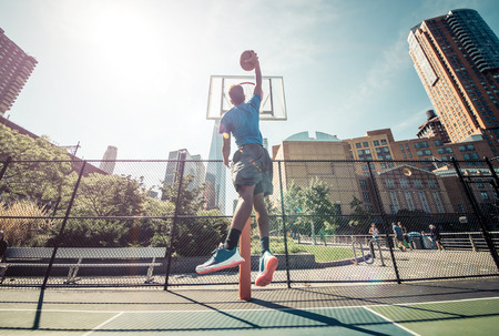 michael: Street basketball athlete performing huge slam dunk on the court, New york buildings background Stock Photo