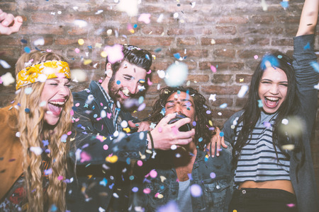 feast: Friends making big party in the night. Four people throwing confetti and drinking champagne