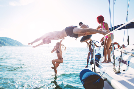 group of friends diving in the water during a boat excursion 스톡 콘텐츠