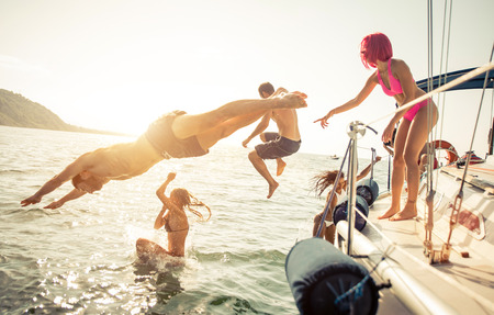 Grupo de amigos de buceo en el agua durante una excursión en barco Foto de archivo - 64360886
