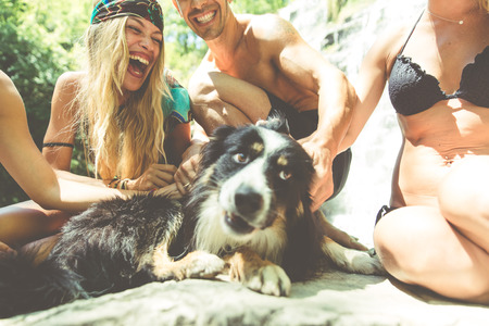 dog rock: Group of friends making excursion in the jungle with waterfall with their dog Stock Photo