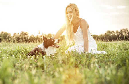 Beautiful blonde woman playing and stroking her loyal border collie