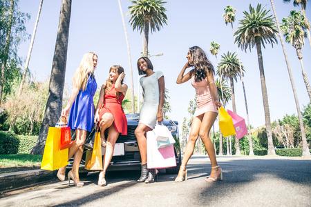 comprando zapatos: Grupo multiétnico de compras niñas - Cuatro mujer hermosa que se divierte mientras que comprar algunos regalos en un centro comercial en Beverly Hills