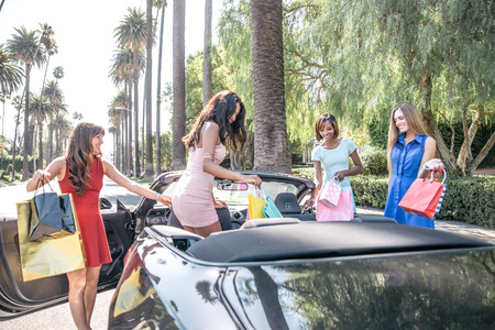 carro supermercado: Multiethnic group of girls shopping - Four beautiful woman having fun while buying some presents in a mall in Beverly Hills