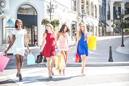 chicas de compras: Grupo multiétnico de compras niñas - Cuatro mujer hermosa que se divierte mientras que comprar algunos regalos en un centro comercial en Beverly Hills