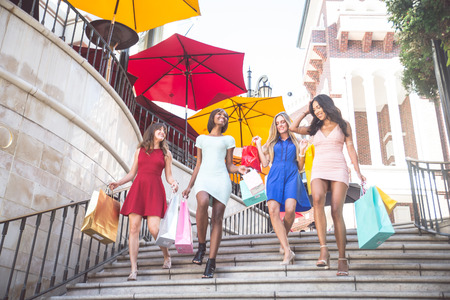 overspending: Multiethnic group of girls shopping - Four beautiful woman having fun while buying some presents in a mall Stock Photo