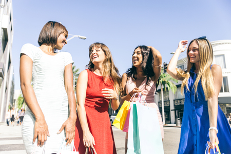 overspending: Multiethnic group of girls shopping - Four beautiful woman having fun while buying some presents in a mall in Beverly Hills