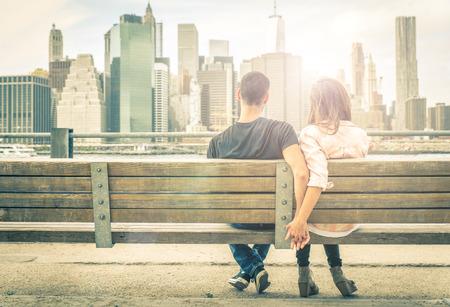 몇 일몰 시간에 스카이 라인의 앞에 뉴욕 벤치에서 휴식. 사랑, 관계, 여행에 대한 개념 스톡 콘텐츠