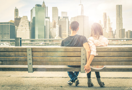 couple relaxing on New york bench in front of the skyline at sunset time. concept about love,relationship, and travel Banco de Imagens - 65081289