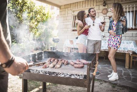 Gruppe von Freunden im Hinterhof machen Grill. Konzept über gute und positive Stimmung mit Freunden