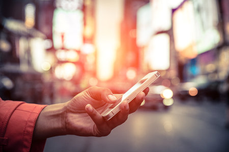 American woman reading message on the smart phone in Time square, Stock Photo