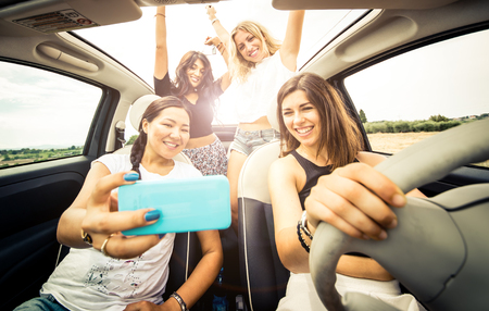 Women having fun driving in a convertible car Stock Photo