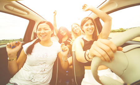 Women having fun driving in a convertible car Imagens