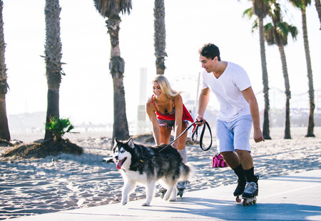 Couple having fun with their rollerskates and playful husky