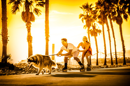 airiness: Couple having fun with their rollerskates and playful husky