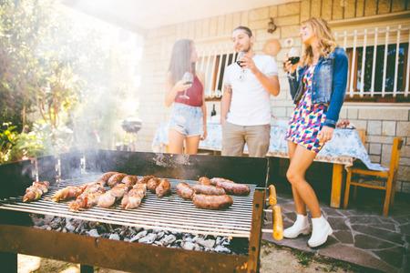 Groep vrienden het maken van barbecue in de achtertuin. Concept over een goede en positieve stemming met vrienden Stockfoto