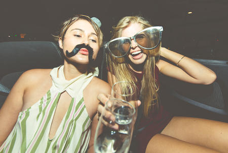 Party girls celebrate in Hollywood drinking champagne on a covertible car Stockfoto