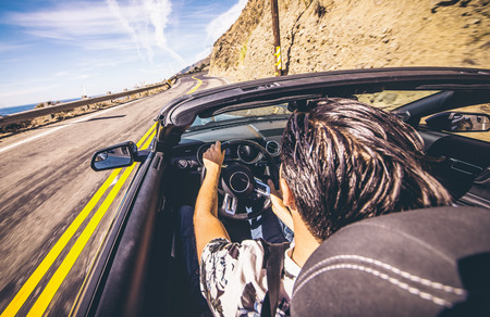 Boy driving his sport convertible car on the coast Stock Photo