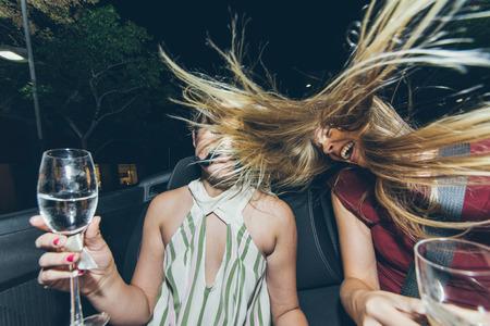 gente loca: muchachas del partido en un coche descapotable se divierten y hacen parte