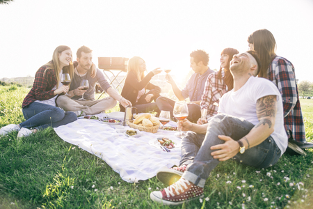 Группа друзей, с удовольствием во время еды и питья в Pic-NIC - Счастливые люди на вечеринке барбекю Фото со стока