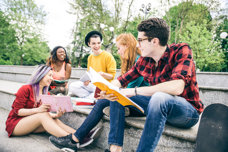 happy asian people: Multi-ethnic group of students stdying together outdoors in a college campus