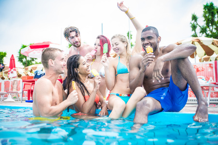 slipway: Multi-ethnic group of friends eating ice cream in a swimming pool - Young happy people having fun and enjoying summertime in a aquapark