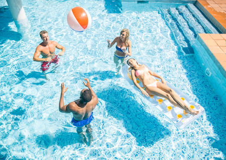 Group of friends playing and relaxing in a swimming pool during summer holidays