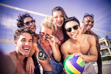 Groep vrienden spelen beach volley en het nemen van een selfie als zomervakantie herinneringen Stockfoto