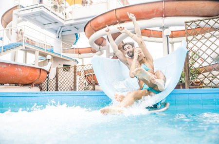 slipway: Friends having fun on a swimming pool slide - Couple splashing into water from a acquapark pipe Stock Photo