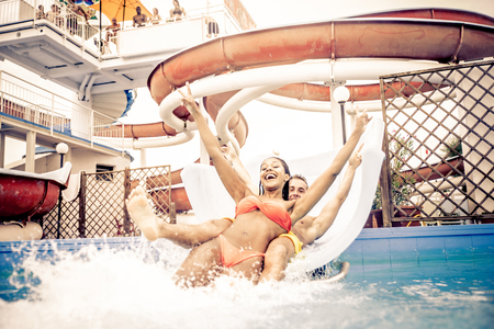 Friends having fun on a swimming pool slide - Couple splashing into water from a acquapark pipe 写真素材