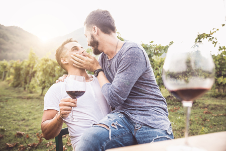 kisses: Gay couple at a romantic date, having fun and drinking wine - Homosexual pair kissing
