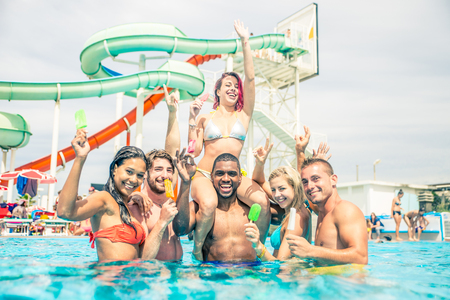 slipway: Group of friends having fun in a waterpark - Young people enjoy summer holiday Stock Photo