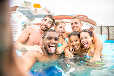 Group of frends taking a selfie in a aqua- park while resting in a swimming pool