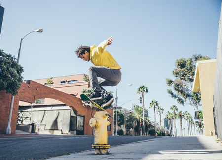 Cool skateboarder jumping over a hydrant on the streets - Afroamerican guy jumping with his skate and performing a trick