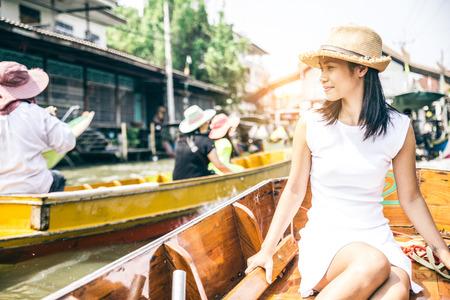 Mujer en un barco en el mercado flotante de Bangkok, Tailandia Foto de archivo - 65091162