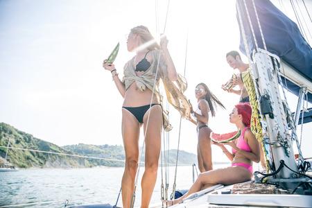 Multiraciale groep vrienden het eten van watermeloen op een zeilboot - Jonge gelukkige mensen zonnen tijdens de zomervakantie
