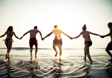 Group of friends making party in the water at sunrise time photo