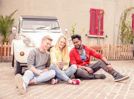 europe vintage: Three friends taking a selfie on a trip with a vintage car - Multi-ethic group of people travelling across europe Stock Photo