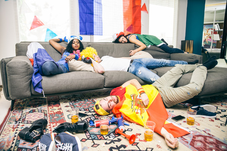 Group of friends sleeping in a living room after party - Drunk supporters resting after celebrating their teams at a sport event