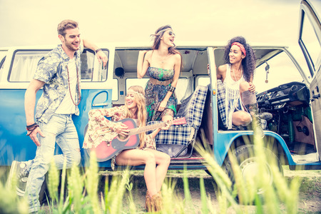 Multi-ethnic group of friends playing guitar and singing on a road trip with a 70s van - Hippies having fun outdoors