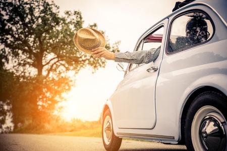 시골에서 여행을 운전하는 자동차의 행복한 커플