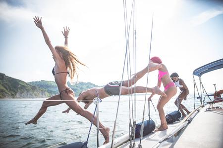 Groep vrienden springen van de boot in de zee - Jonge mensen met plezier op een excursie op een zeilboot Stockfoto