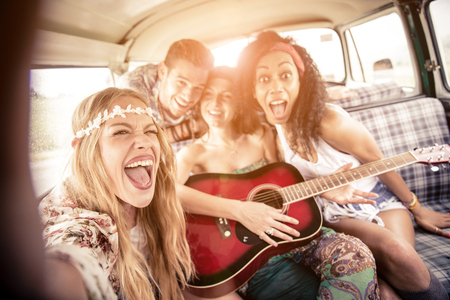 Group of friends traveling in a 70s van - Happy young people taking a selfie and having fun