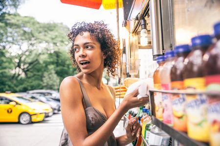 Hübsche Frau, die einen Hotdog in einem Kiosk in New York kauft