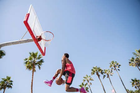 Basketball player making a dunk - Sportive man doing a spectacular dunk outdoors Stock Photo