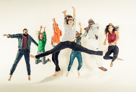 Multi-ethnic group of friends jumping on white background, studio shot